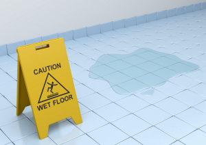 Photo of wet floor sign next to a water spill